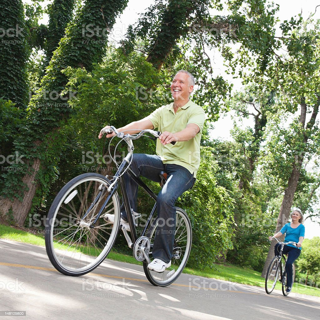 Happy Man and Woman Biking Down a Trail royalty-free stock photo