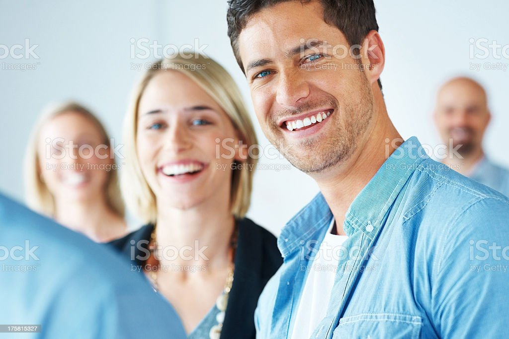 Happy man and woman smiling together with colleagues stock photo