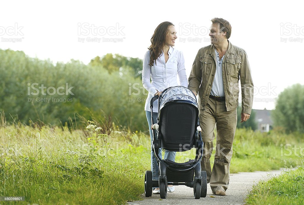 Happy man and woman walking with baby pram outdoors royalty-free stock photo