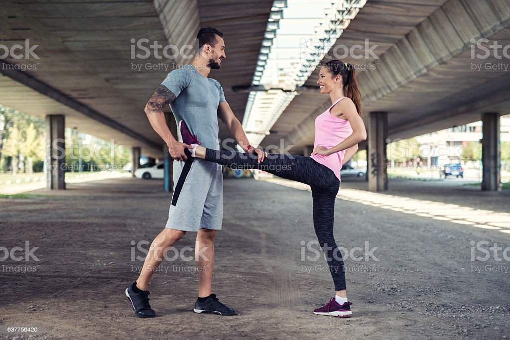Happy man assisting young woman in stretching exercises. stock photo