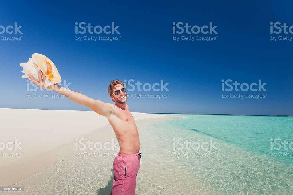 happy man beach sea shell summer holiday stock photo