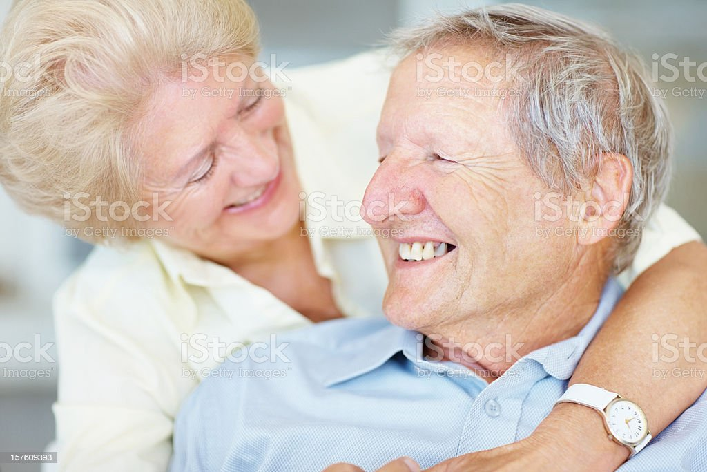 Happy man being hugged by a senior woman from behind royalty-free stock photo