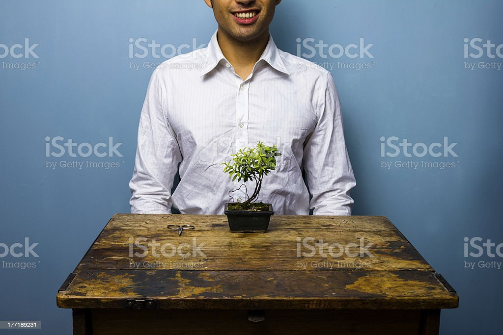 Happy man caring for a bonsai tree royalty-free stock photo