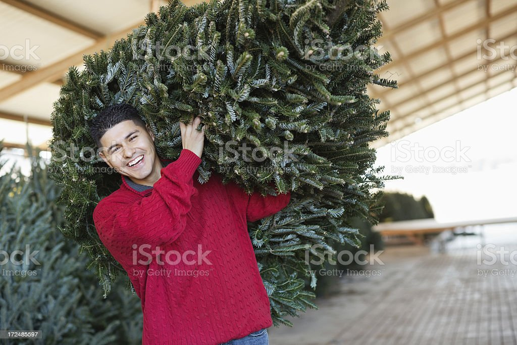 Happy man carrying Christmas tree to car after purchasing stock photo