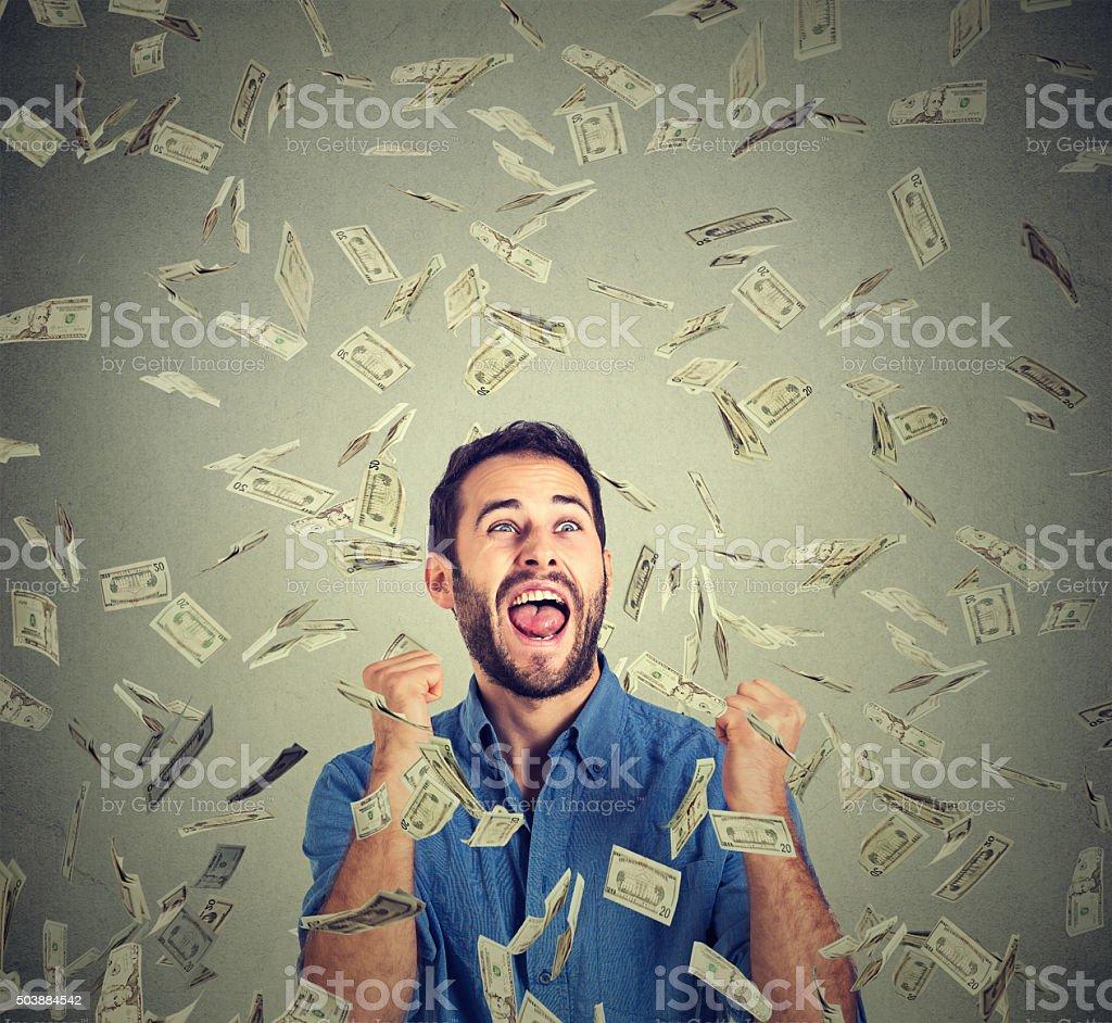 happy man celebrates success screaming under money rain stock photo