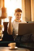Happy man celebrating while using laptop at home.