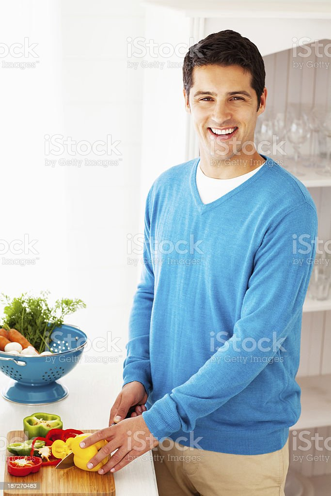 Happy Man Cutting Yellow Bell Pepper royalty-free stock photo