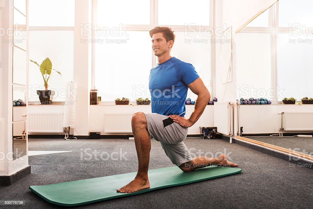 Happy man doing stretching exercises in a health club. stock photo