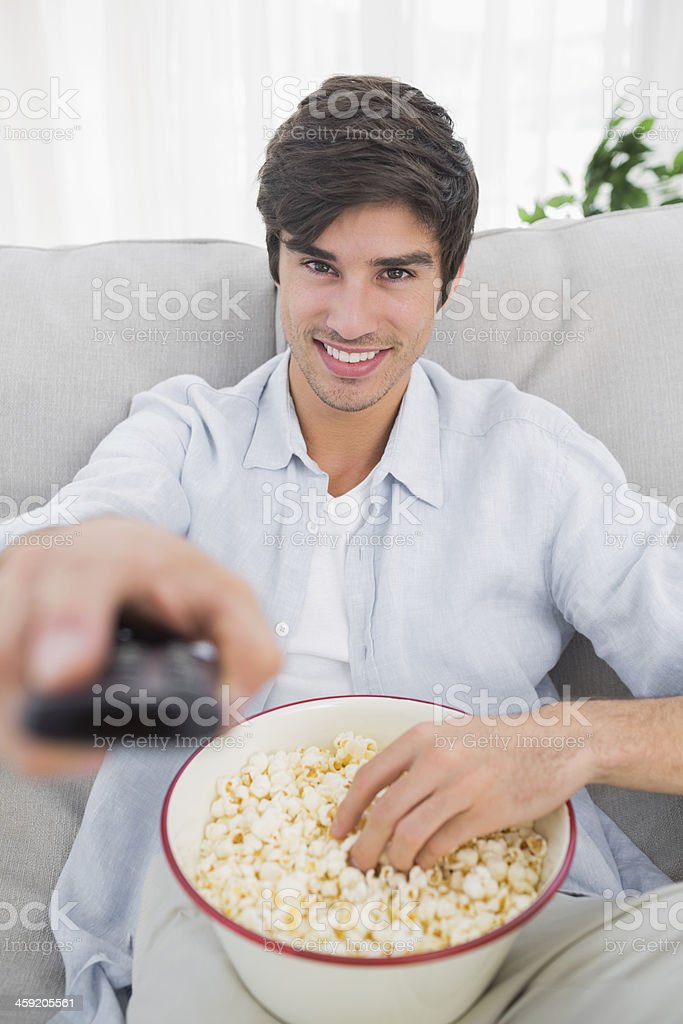 Happy man eating popcorn and holding remote control royalty-free stock photo