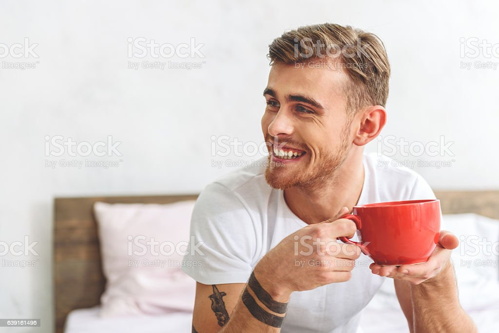 Happy man enjoying hot drink stock photo