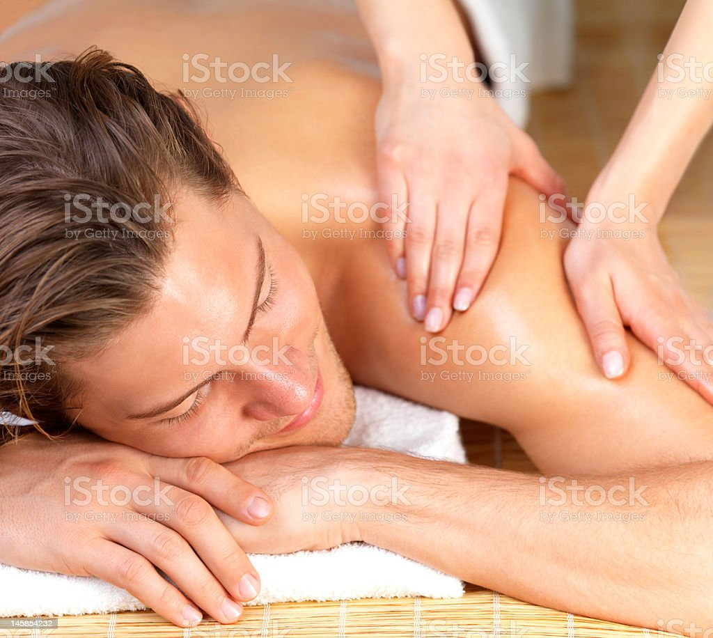 Happy man getting massage at spa royalty-free stock photo