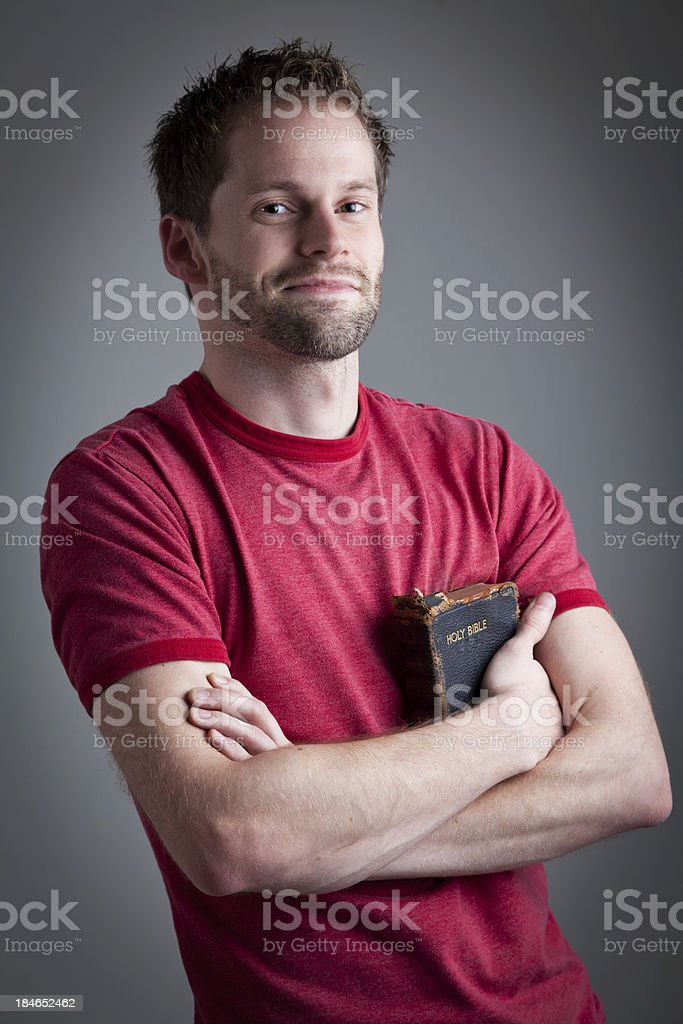 Happy man holding his old used bible royalty-free stock photo