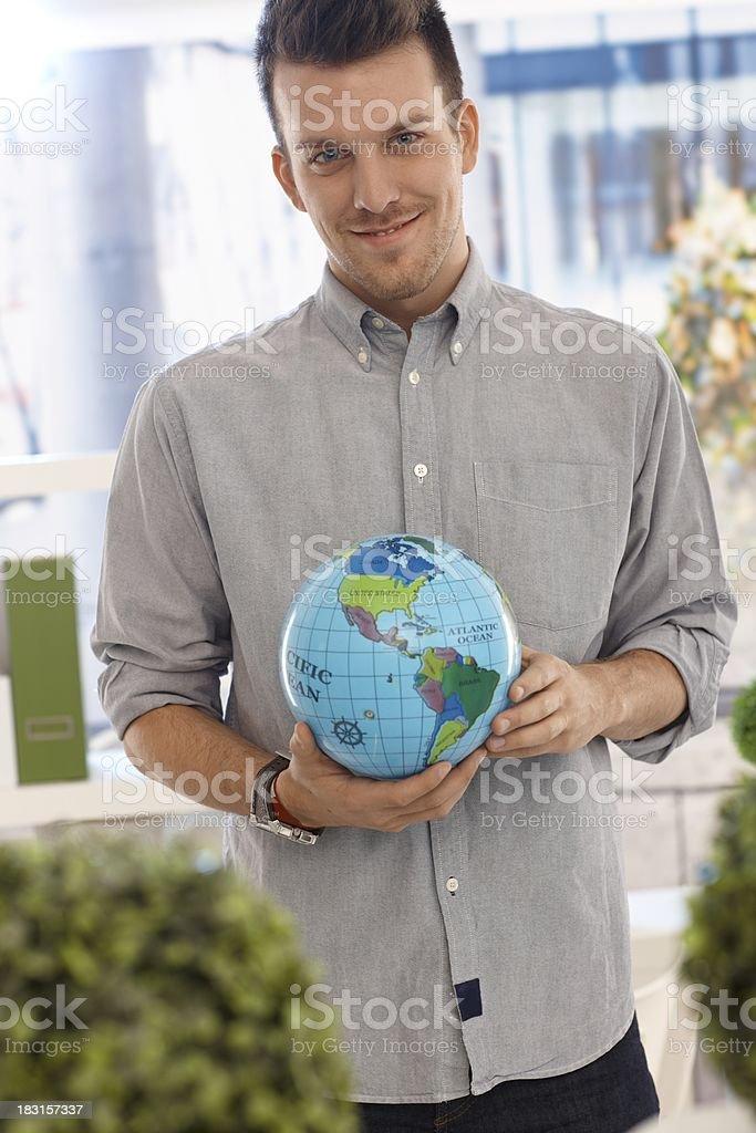 Happy man holding small globe royalty-free stock photo
