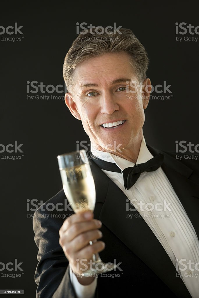 Happy Man In Tuxedo Toasting Champagne Flute royalty-free stock photo