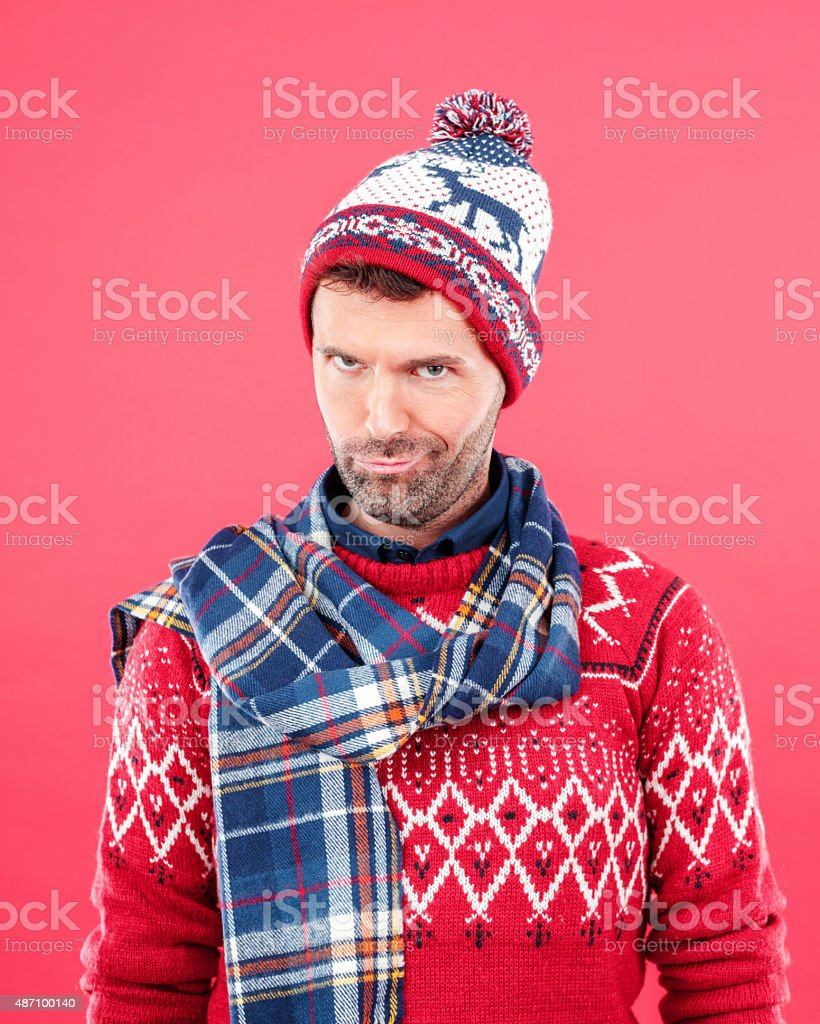 Happy man in winter outfit against red background stock photo