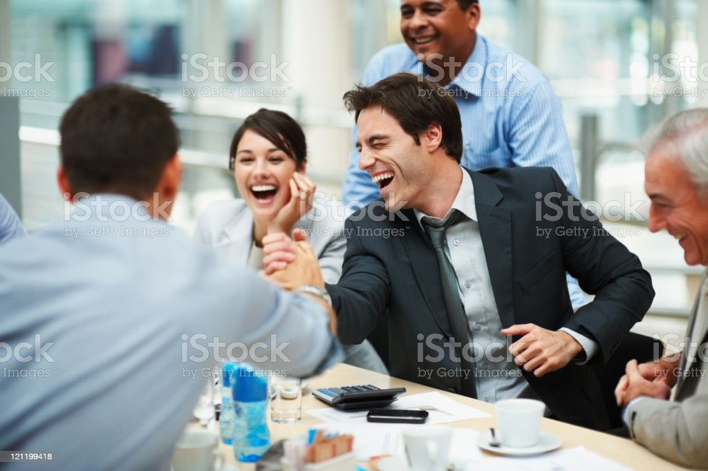 Happy man joining hands in unity with colleague at meeting stock photo
