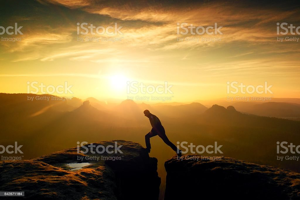 Happy man  jumping between rocks, misty mountains. stock photo