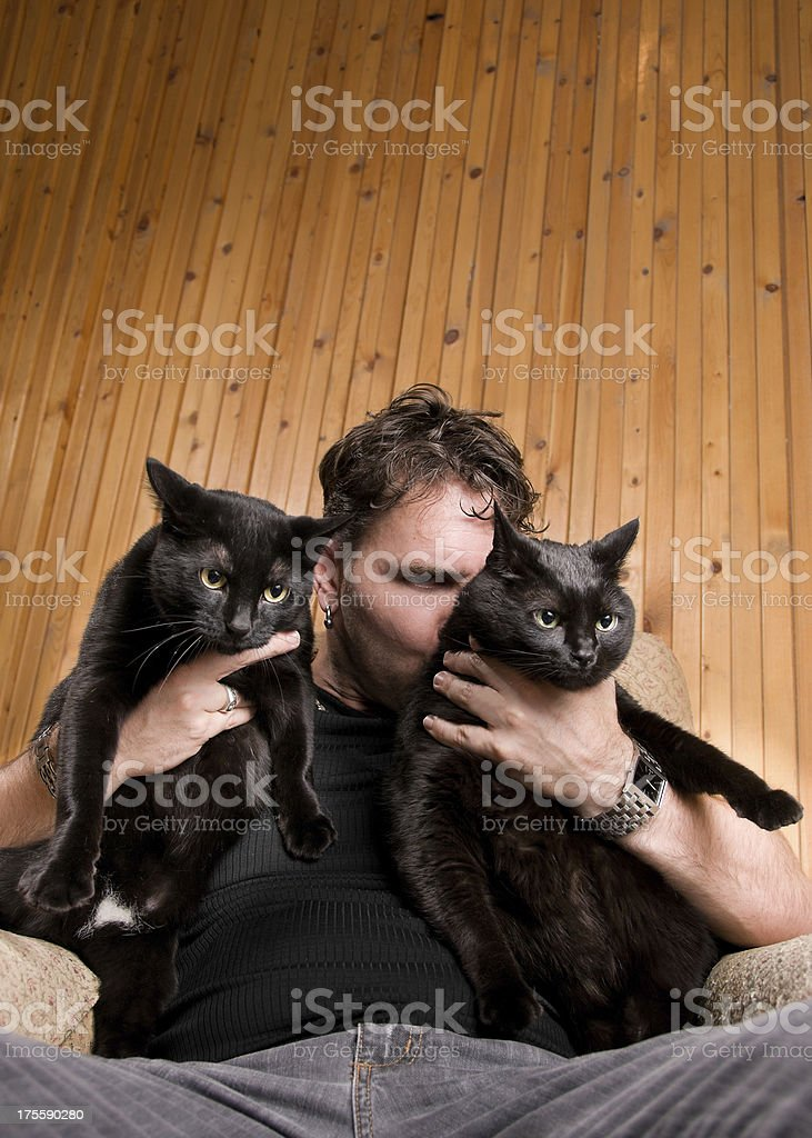 Happy Man Kissing Two Black Cats stock photo
