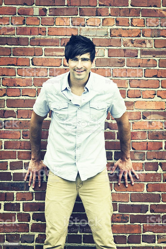 Happy Man Leaning Against Brick Wall stock photo
