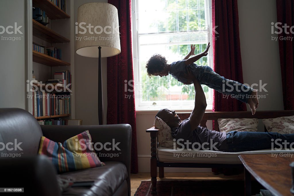 Happy man lifting daughter while lying on seat stock photo