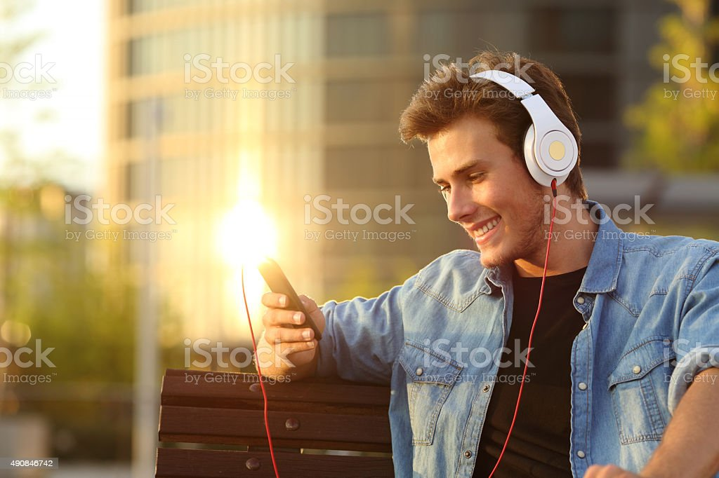 Happy man listening to music from a smart phone stock photo