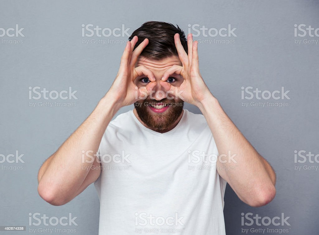 Happy man looking at camera through fingers stock photo