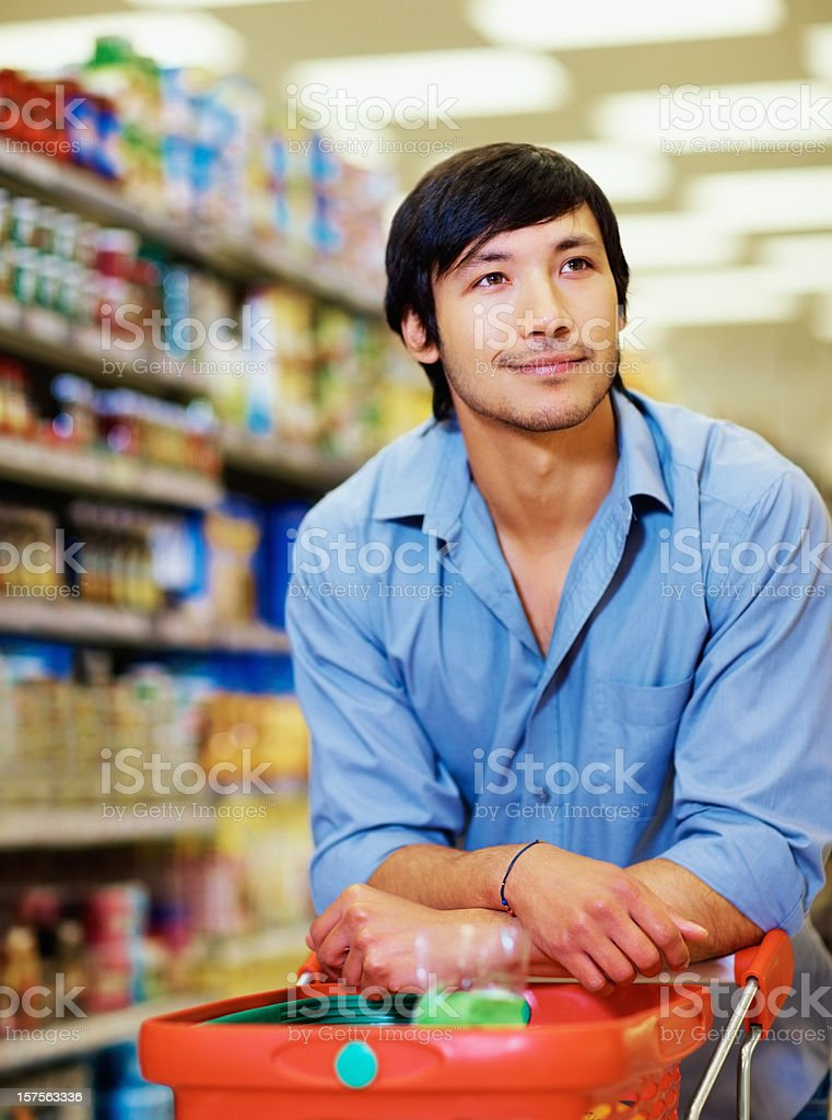 Happy man looking out for goods at the supermarket royalty-free stock photo