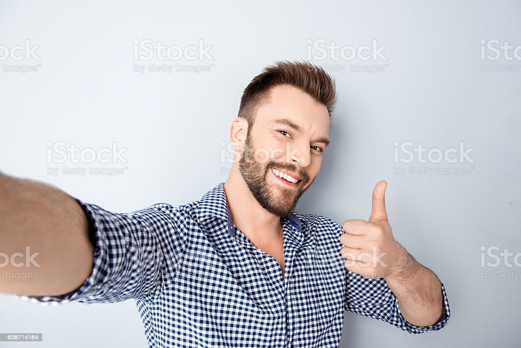 Happy man making selfie and showing thumb up stock photo