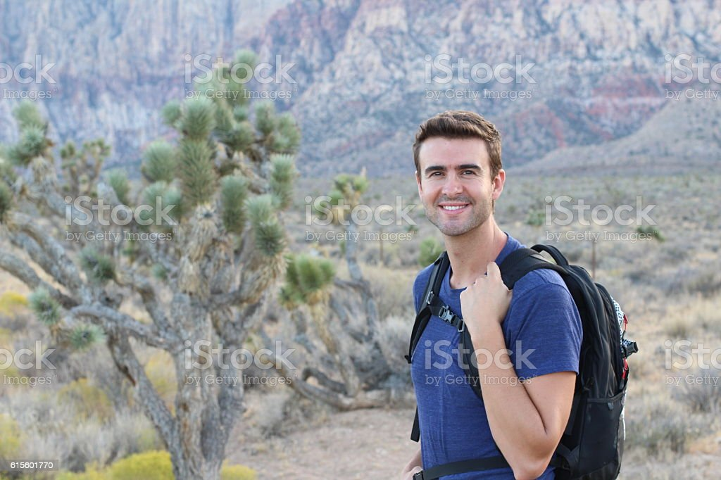 Happy man mountain hiker with backpack stock photo