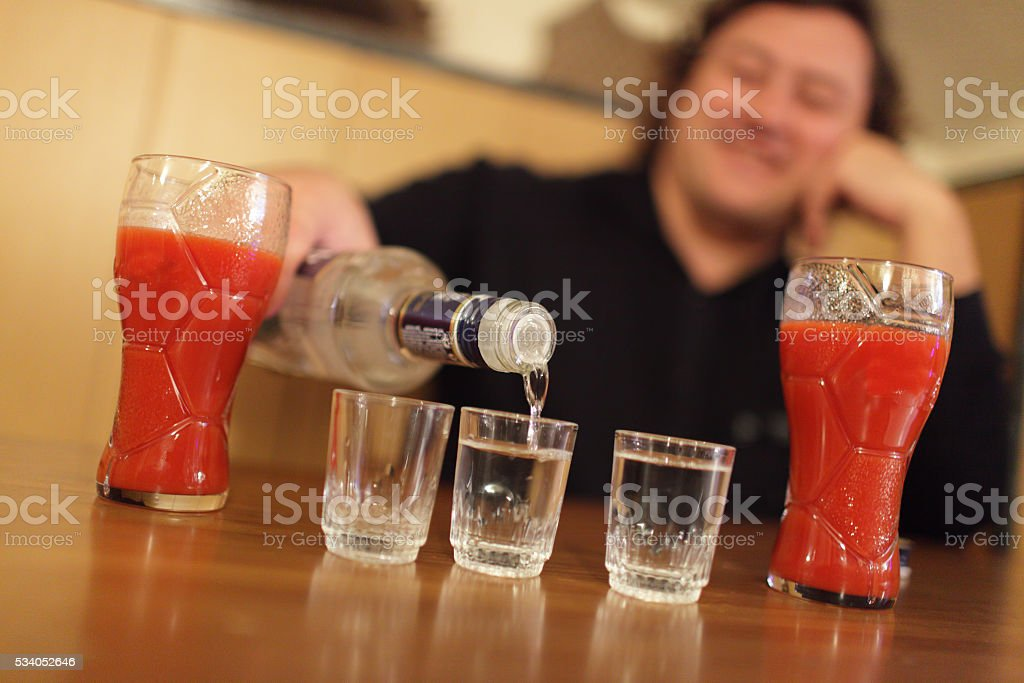 Happy man pouring vodka stock photo