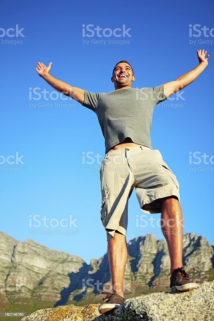 Happy man raising hands aganist clear blue sky royalty-free stock photo
