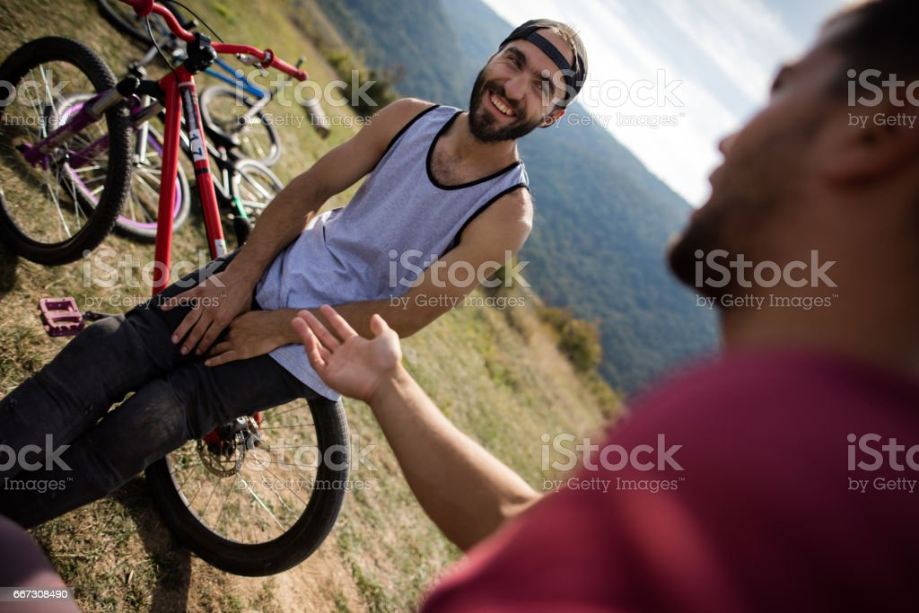 Happy man relaxing on mountain bike while talking with friend. stock photo