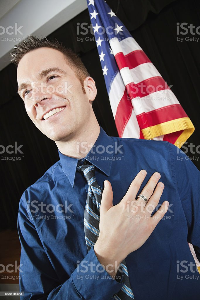 Happy Man Saying Pledge of Allegiance With American Flag stock photo