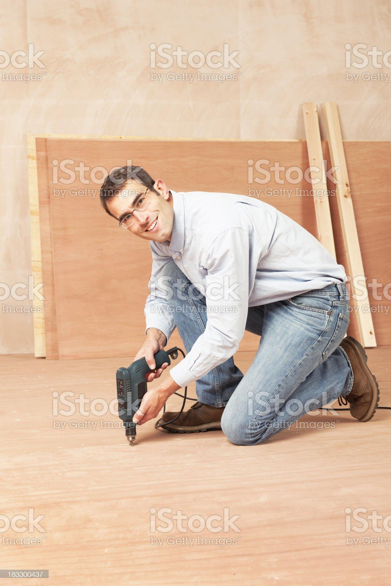 Happy man screwing down ply flooring royalty-free stock photo