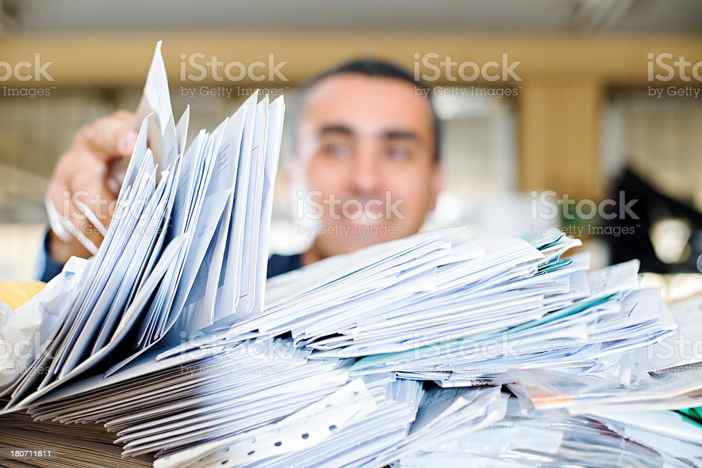 Happy man searching a close-up pile of mail for his letter stock photo