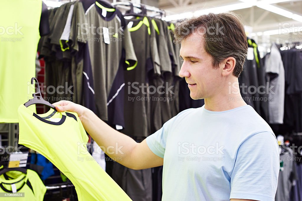 Happy man shopping for sport t-shirt in shop stock photo