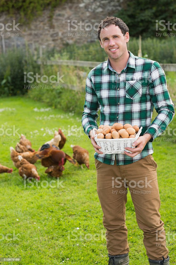 Happy man showing a basket filled with eggs stock photo