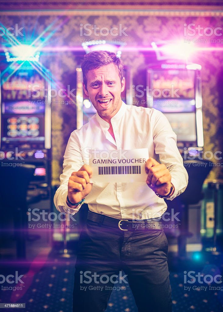Happy Man Showing a Gaming Voucher. Slot Machine on the background.