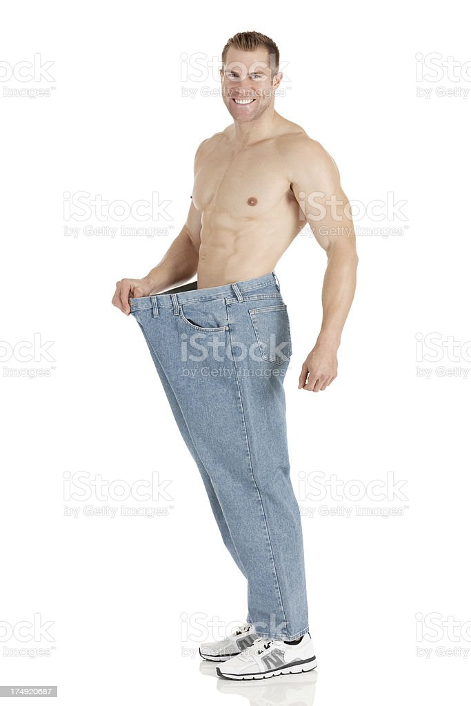 Happy man showing his weight loss royalty-free stock photo