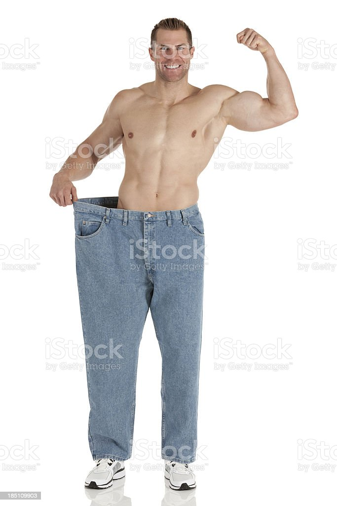 Happy man showing off his weight loss royalty-free stock photo