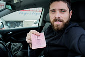 Happy man shows french driver licence