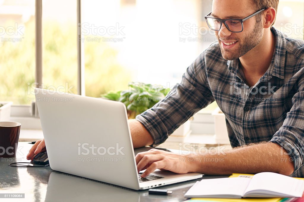 Happy young man, wearing glasses and smiling, as he works on his...