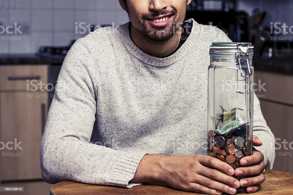 Happy man sitting in kitchen with piggy bank royalty-free stock photo