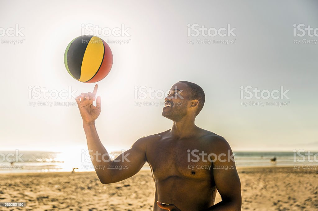 Happy man spinning ball at beach against clear sky stock photo