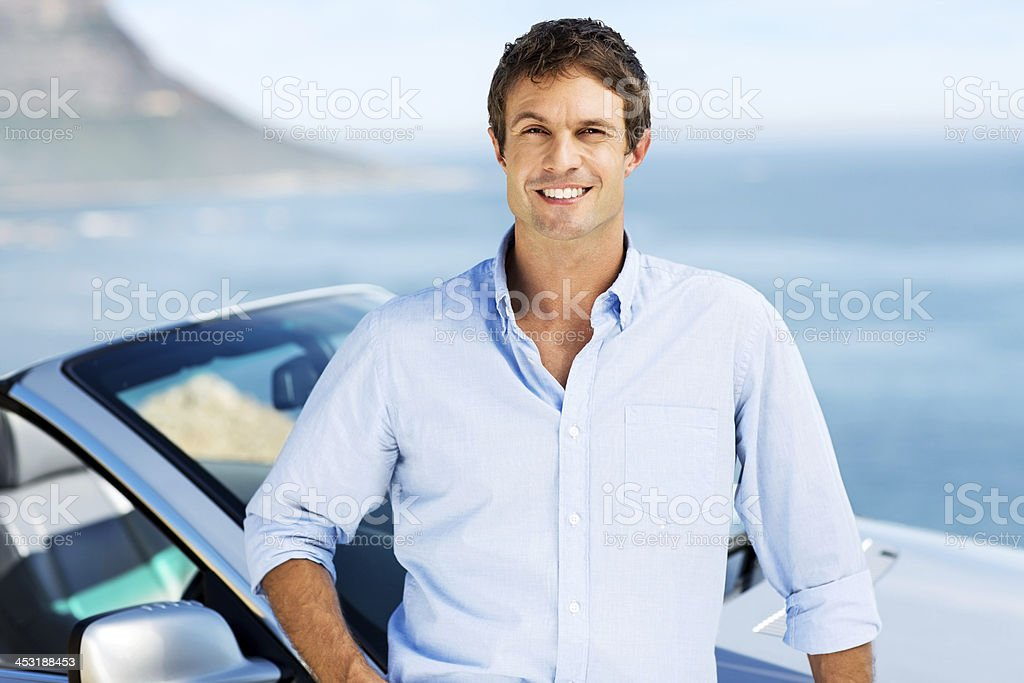 Happy Man Standing Against Convertible Car royalty-free stock photo