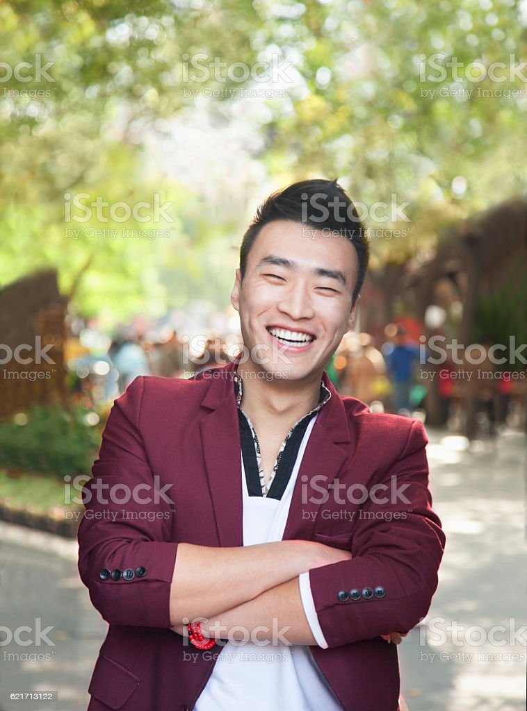 Happy man standing confidently at festival stock photo