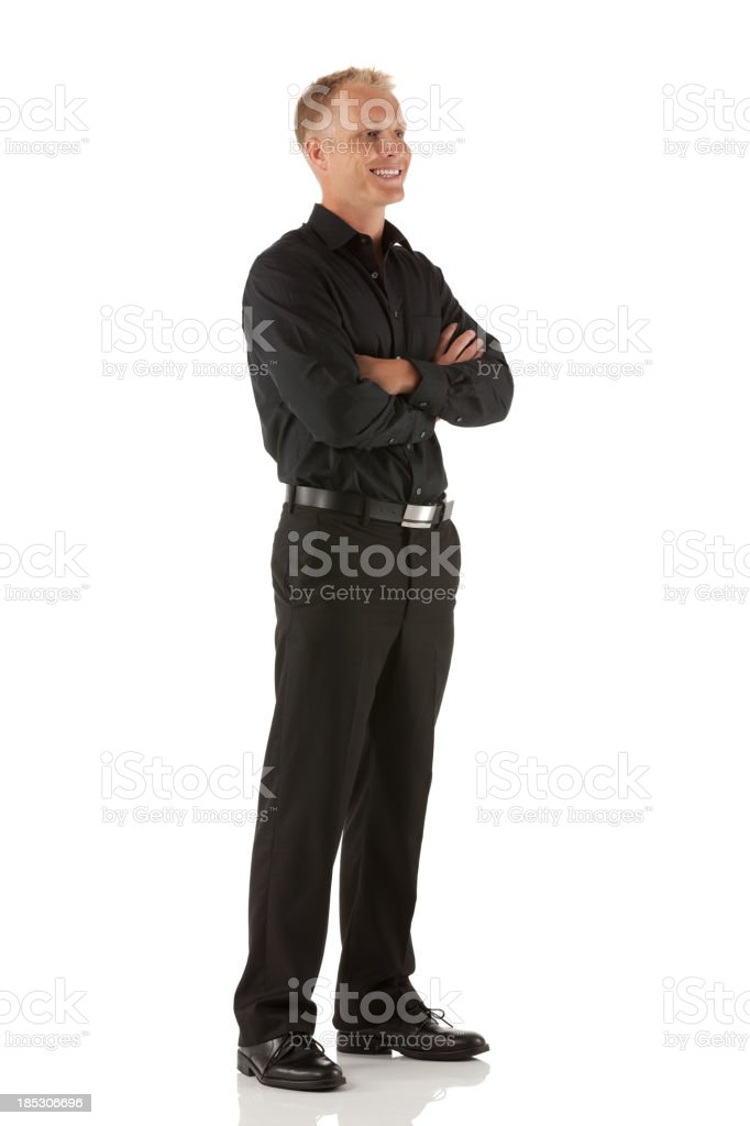 Happy man standing with his arms crossed stock photo