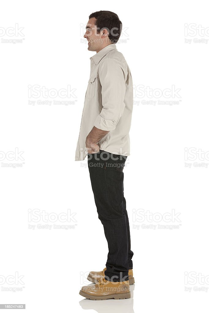Happy man standing with his hands in pockets stock photo