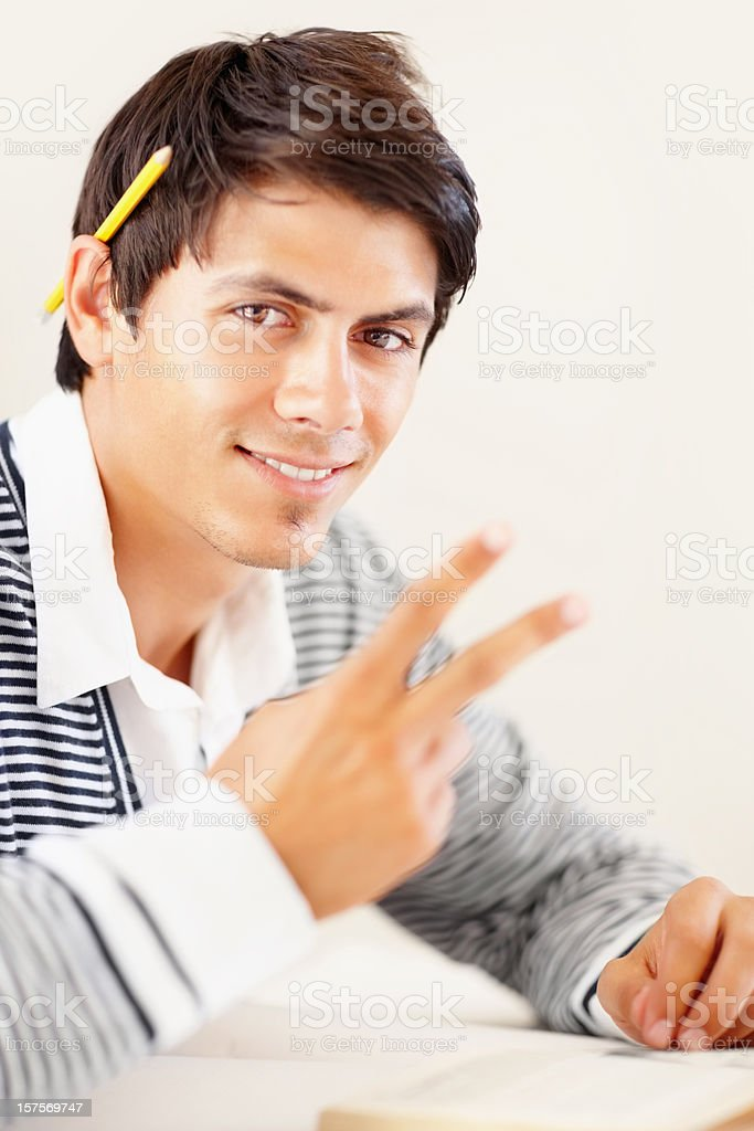 Happy man studying and gesturing a peace sign royalty-free stock photo