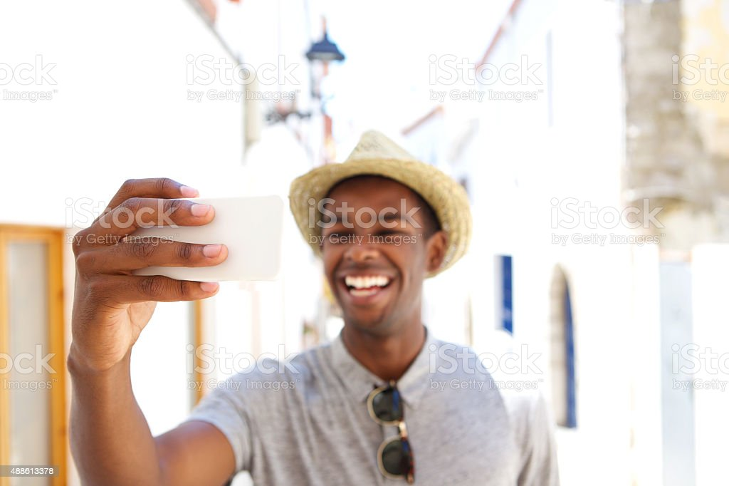 Happy man taking selfie on vacation stock photo
